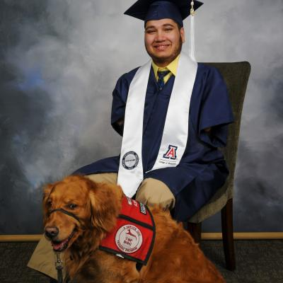 photo of Samir in graduation robe with his service dog